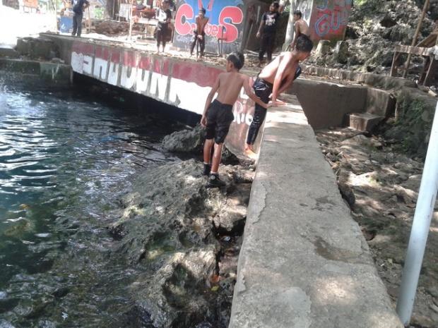 Mandi di mata air Sodong dengan celana dan sepatu sekolah.